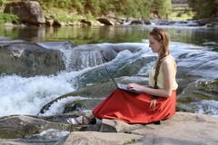 Beautiful long-haired girl in red skirt with laptop sitting on a rock on a background of mountain river cascade. Freelance concept royalty free stock image