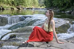Beautiful long-haired girl in a red skirt sitting on a rock on a background of mountain river cascade. Summer evening. Tranquility royalty free stock photo