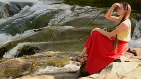 Beautiful long-haired girl in a red skirt sitting on a rock on a background of mountain river cascade. Summer evening. Tranquility. And enjoyment of nature stock video footage