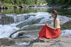 Beautiful long-haired girl in a red skirt with a smartphone sitting on a rock on a background of mountain river cascade. Summer stock photos