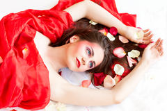 Beautiful long-haired girl is relaxing in rose petals Royalty Free Stock Photo