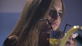 Beautiful long-haired girl sits and drinks a cold alcoholic cocktail stock footage