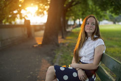 Beautiful  long haired girl sitting in a Park during golden sunset. Stock Photography