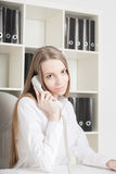The beautiful long-haired girl speaks at office by phone Royalty Free Stock Image