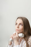 The beautiful long-haired girl speaks at office by phone Stock Image