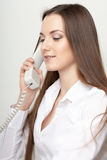 The beautiful long-haired girl speaks at office by phone Stock Photo