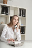 The beautiful long-haired girl speaks at office by phone Royalty Free Stock Photos