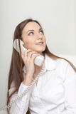 The beautiful long-haired girl speaks at office by phone Royalty Free Stock Images