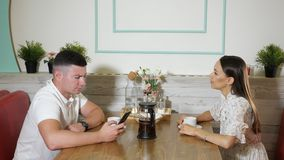 Girl talks with guy using smartphone at table in cozy cafe. Beautiful long haired girl talks with young guy using smartphone sitting at served table in cozy stock footage