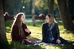 A beautiful long-haired girl tells a story to her friend. They sit on a plaid in the autumn park royalty free stock photos