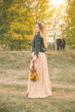 Beautiful long-haired girl with violin in nature park during sunset time Stock Photo