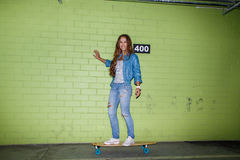 Beautiful long-haired girl with a wooden skateboard near a green Stock Photography