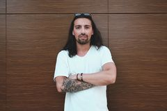 Attractive man crossed hands. Beautiful long haired man with beard and tattoos posing on a wood wall with crossed arms while looking to camera, looking to right Royalty Free Stock Photography