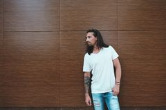Attractive man with beard and long hair portrait. Beautiful long haired man with beard and tattoos posing on a wood wall with crossed arms while looking to Stock Photos