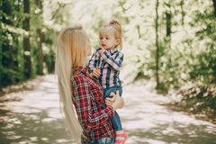 Mother with child. Beautiful long-haired mom walking in the woods with her little daughter royalty free stock images