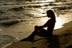 Beautiful, long haired slim young woman at the beach, sunset Stock Image