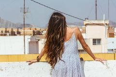 Beautiful long-haired woman looking at the city on the sky line, Royalty Free Stock Photos