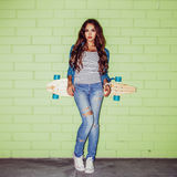 Beautiful long-haired woman with a wooden longboard near a green royalty free stock photography