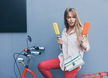 Beautiful long-haired young blonde woman makes a choice of ice cream sitting on a red vintage bike stock photography