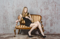 Beautiful long-haired young blonde woman with a slender figure in a black mini dress Royalty Free Stock Photo
