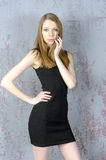 Beautiful long-haired young blonde woman with a slender figure in a black mini dress Stock Photos