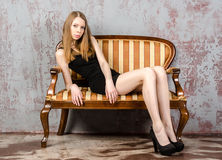 Beautiful long-haired young blonde woman with a slender figure in a black mini dress Royalty Free Stock Images