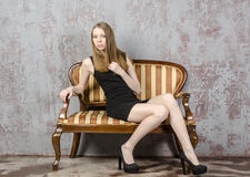 Beautiful long-haired young blonde woman with a slender figure in a black mini dress Stock Image