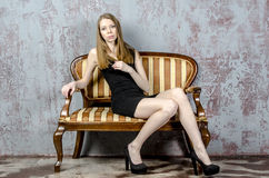Beautiful long-haired young blonde woman with a slender figure in a black mini dress Stock Photo