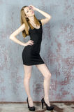 Beautiful long-haired young blonde woman with a slender figure in a black mini dress Royalty Free Stock Image