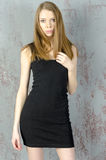 Beautiful long-haired young blonde woman with a slender figure in a black mini dress Royalty Free Stock Photos