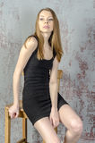 Beautiful long-haired young blonde woman with a slender figure in a black mini dress Stock Photography