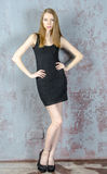 Beautiful long-haired young blonde woman with a slender figure in a black mini dress Royalty Free Stock Photography