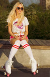 Beautiful long-haired young blonde woman in a vintage roller skates, sunglasses, T-shirt shorts sitting on a hot summer day on the Stock Photography