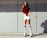 Beautiful long-legged asian girl skating in roller skates and enjoying an ice cream on a summer day Royalty Free Stock Images