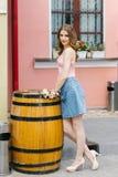Beautiful long-legged cute model girl standing near a decorative oak barrel in the city