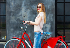 Beautiful long-legged girl posing with red vintage bicycle. She has a smartphone in her jeans pocket Stock Photos