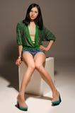 Beautiful long-legged young woman posing sitting Royalty Free Stock Images