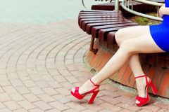 Beautiful long legs girl in red shoes in blue dress sits in the city Royalty Free Stock Photos