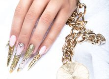 Beautiful long nails in a gold design with Royalty Free Stock Photography