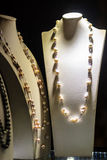 Beautiful long pearl necklaces are displayed at a jewelry shop. Royalty Free Stock Photography