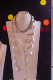 Beautiful long pearl necklaces are displayed at a jewelry shop. Royalty Free Stock Images