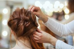 Beautiful, with long, red-haired hairy girl, hairdresser weaves a French braid royalty free stock image