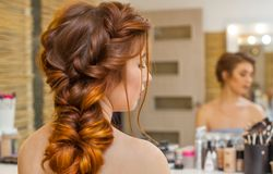 Beautiful, with long, red-haired hairy girl, hairdresser weaves a French braid, in a beauty salon. stock photo