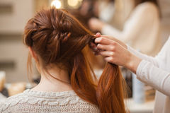 Beautiful, with long, red-haired hairy girl, hairdresser weaves a French braid, in a beauty salon. Stock Images