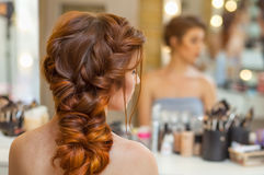 Beautiful, with long, red-haired hairy girl, hairdresser weaves a French braid, in a beauty salon. Professional hair care and creating hairstyles stock photos