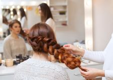 Beautiful, with long, red-haired hairy girl, hairdresser weaves a French braid stock image