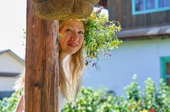 Beautiful long-white hair woman in white dress and flower wreath peeking playfully from behind a wooden pillar on yard of your stock images