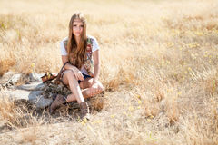 Beautiful longhair hippie girl sitting on a tree stump Royalty Free Stock Photos