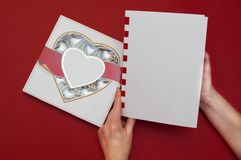 Beautiful love concept for Valentines day. Romantic box of sweets and modern note book with female hands on the red. Beautiful love concept for Valentines day Stock Image