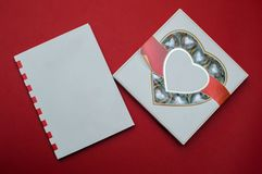 Beautiful love concept for Valentines day. Romantic box of sweets and modern note book on the red background. Beautiful love concept for Valentines day Stock Image